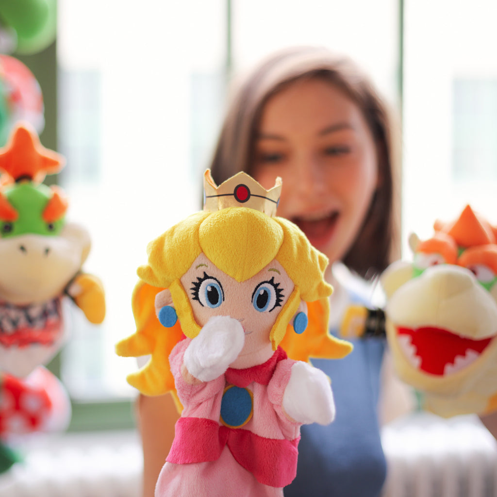 Super Mario Bros: model with Princess Peach, while Bowser and Bowser JR puppets are lurking in the background