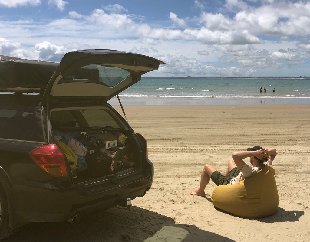 Andy Bowie relaxing next to car at beach