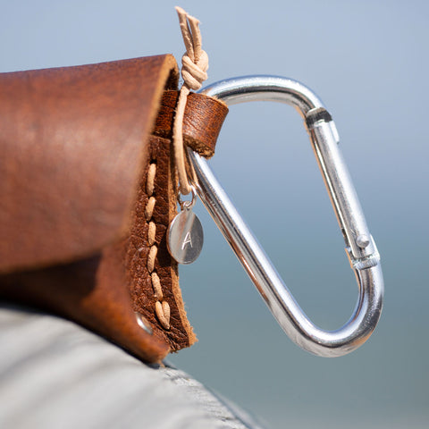 Custom metal tag on brown leather pouch contain natural healing oils.