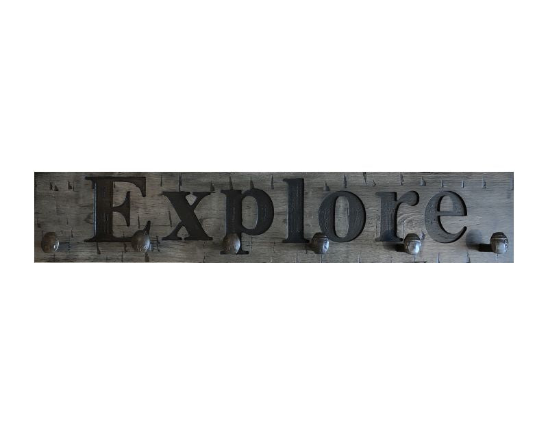 Wood wall coat rack with the words Explore in burned letters. Reclaimed wood and railroad spikes as hooks.
