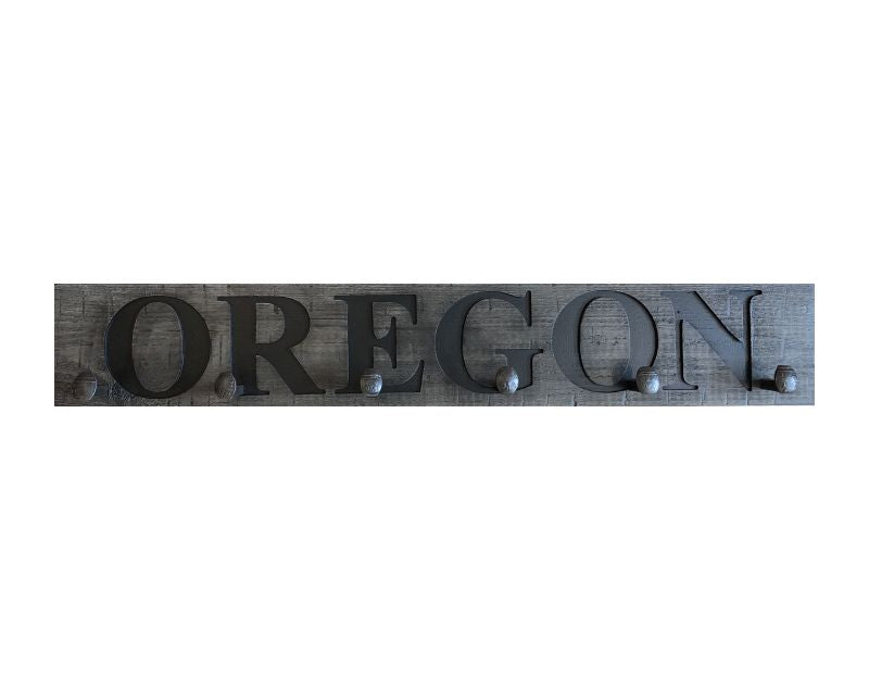 Wood wall coat rack with the words Oregon, in burned letters. Reclaimed wood and railroad spikes as hooks.