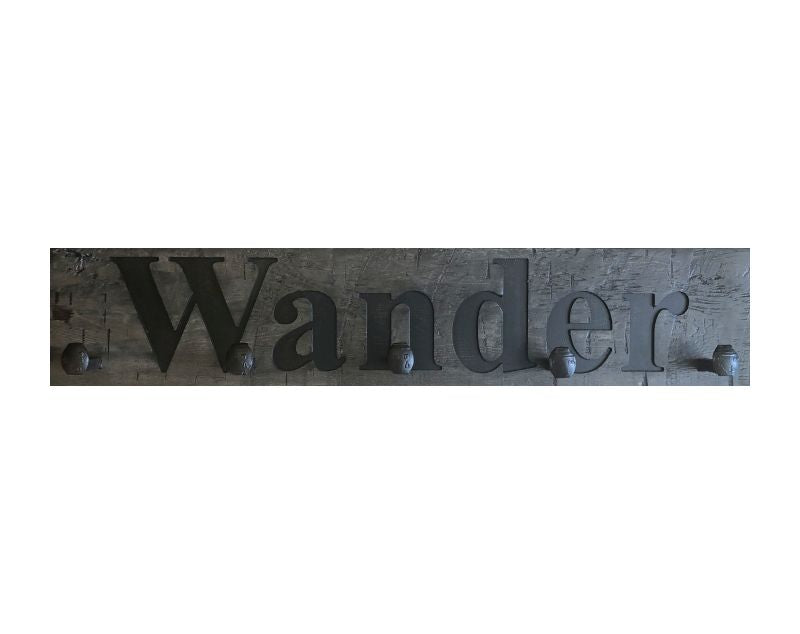 Wood wall coat rack with the words Wander, in burned letters. Reclaimed wood and railroad spikes as hooks.