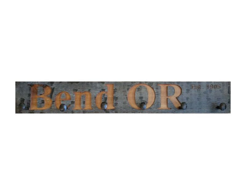 Wood wall coat rack with the words Bend, OR in burned letters. Reclaimed wood and railroad spikes as hooks.