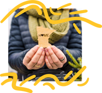 hands holding carved wooden cutout of the state of minnesota with the word home with a heart as the o. the image has an overlay of yellow hand-drawn lines