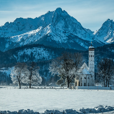 A picture of a snow covered church with a mountain behind it