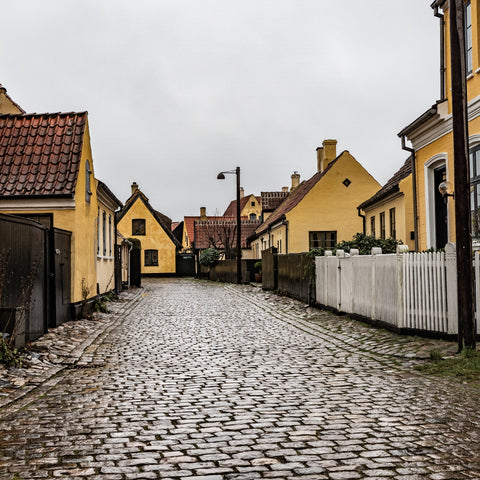 A cobbled sidewalk in between yellow houses
