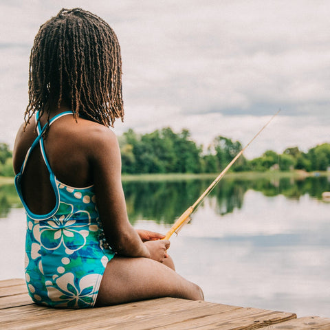 A young girl sitting on a dock with a small fishing pole