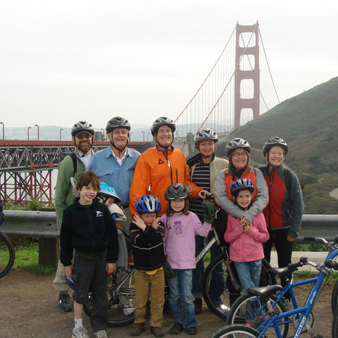 A photo of a group of people with bike helmet on in front of the golden gate bridge