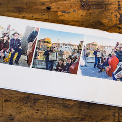 An open Luminta Photobook with 3 pictures of people playing music and laughing