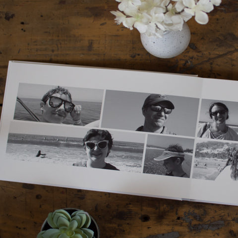 An open Luminta Photobook with a collage of different people at the beach