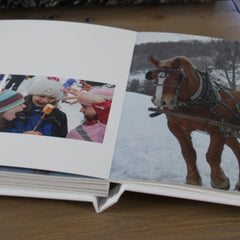 An open Luminta photobook showing children making smores and a horse-drawn carriage