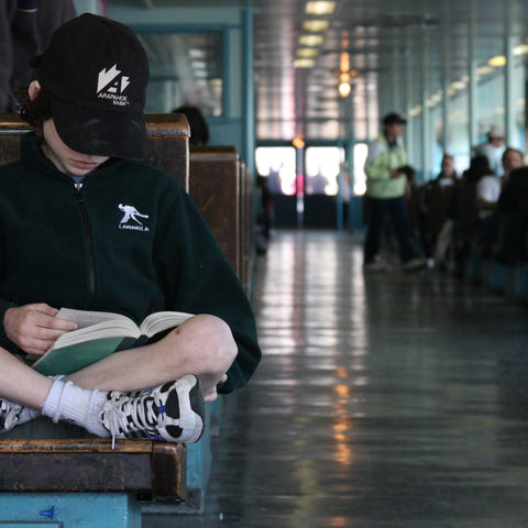 A child reading a book on a bench