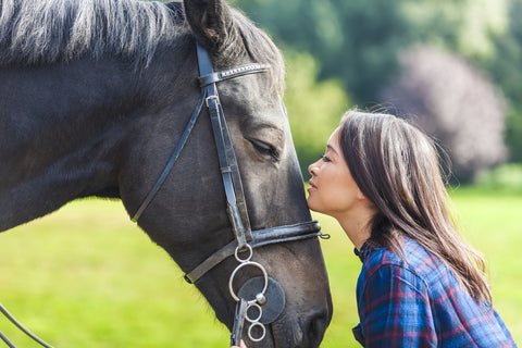 Women kissing her horse on his nose