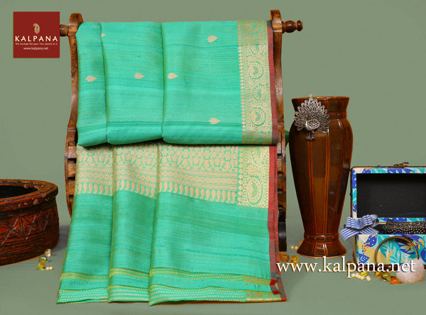 Banarsi Handloom Pure Tussar Saree with All Over Woven Motifs and Woven Zari Border. The Palla is  Woven Zari. It comes with Self Colored Woven Unstitched Blouse with Woven Border. Perfect for Formal Wear.  Recommended for Autumn & Winter season(s). Dry Clean Only