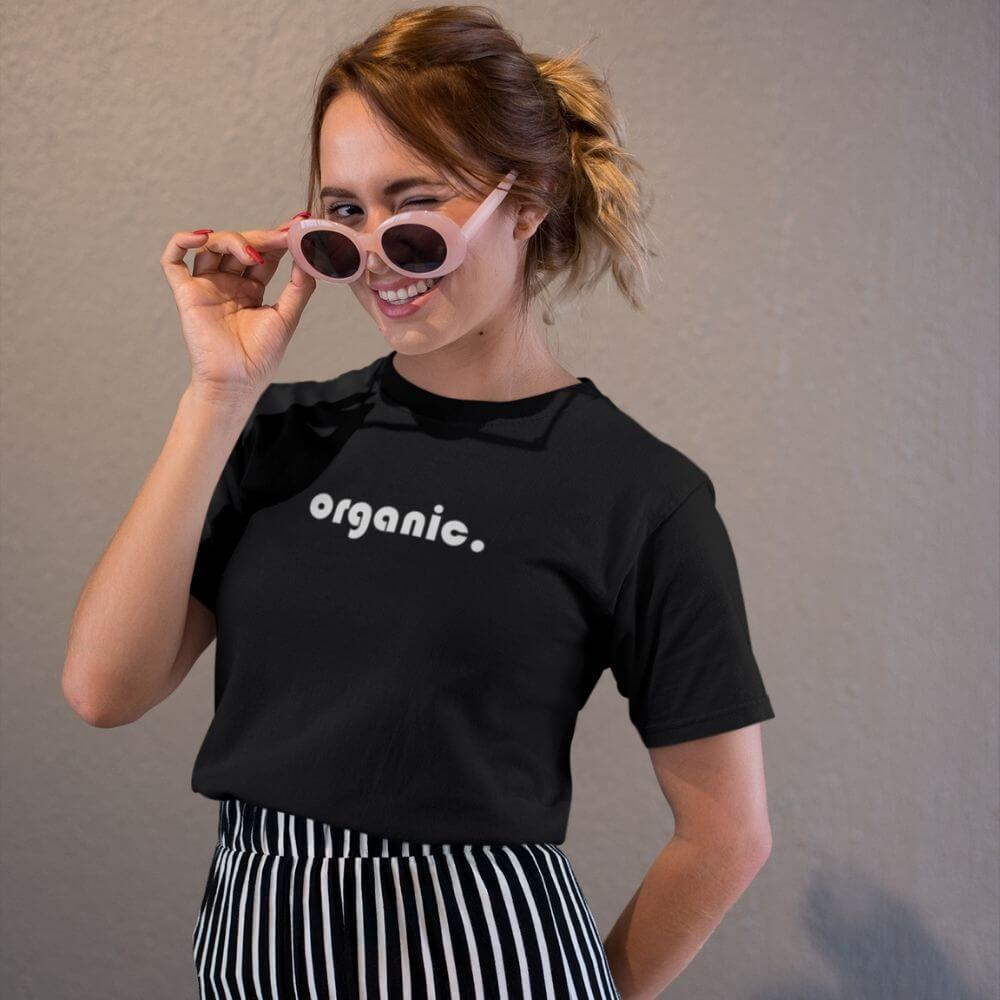 Woman wearing pink sunglasses and black shirt that says organic