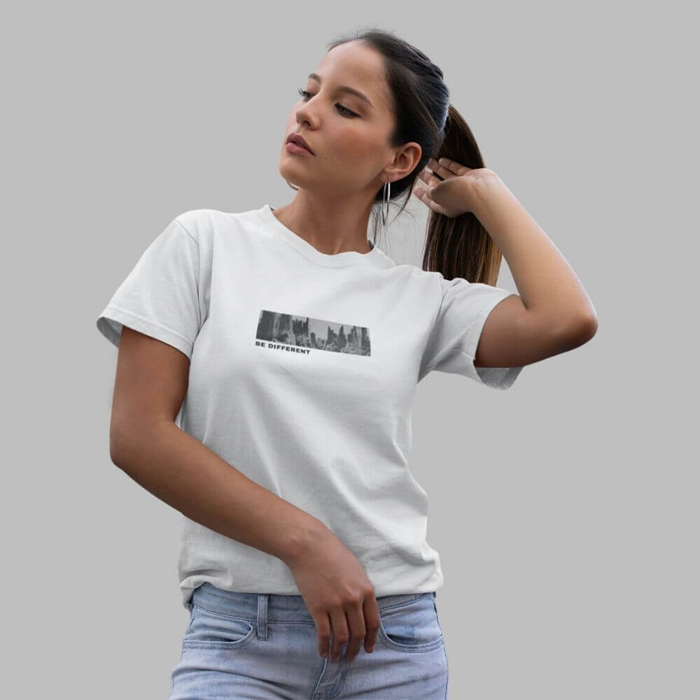 Woman wearing white shirt with canyon design that says be different