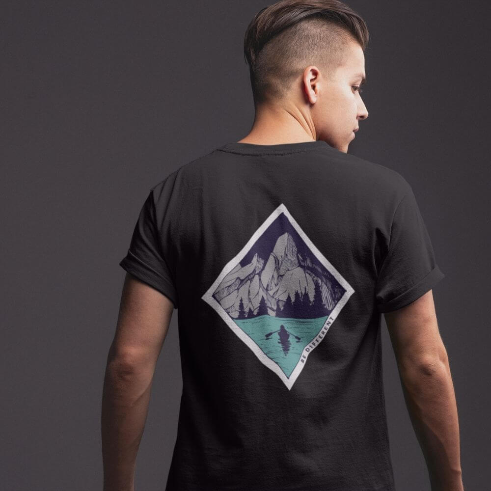 Man wearing shirt with mountains and water that says be different