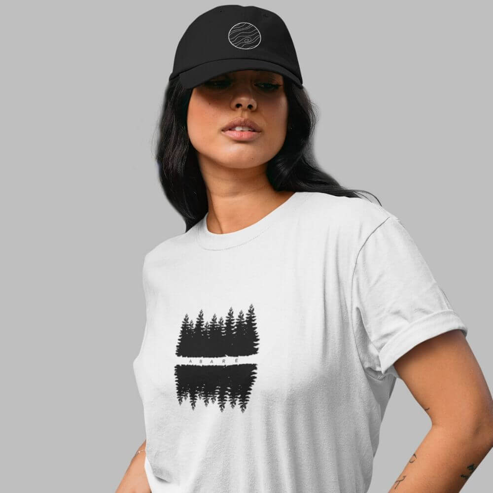 Woman wearing black hat and white shirt with forest design