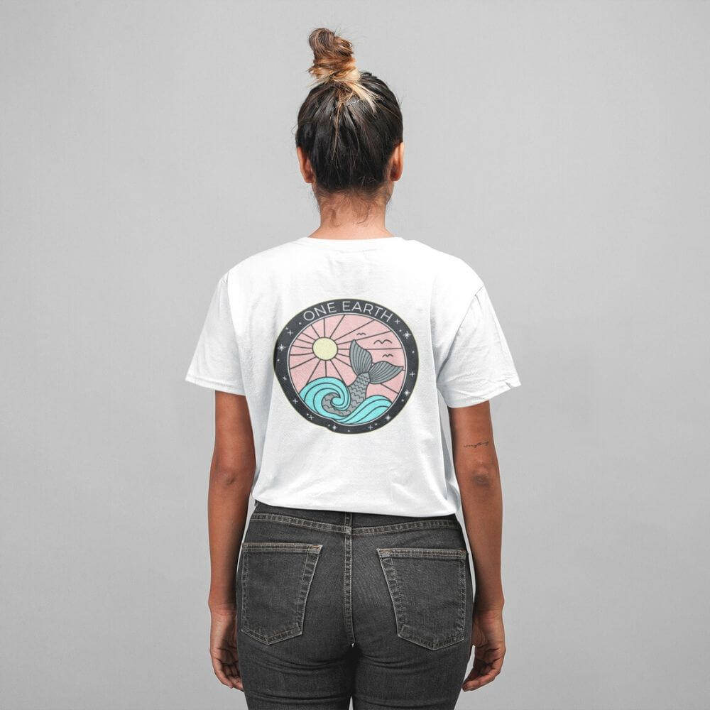 Woman wearing white shirt with ocean design that says one earth