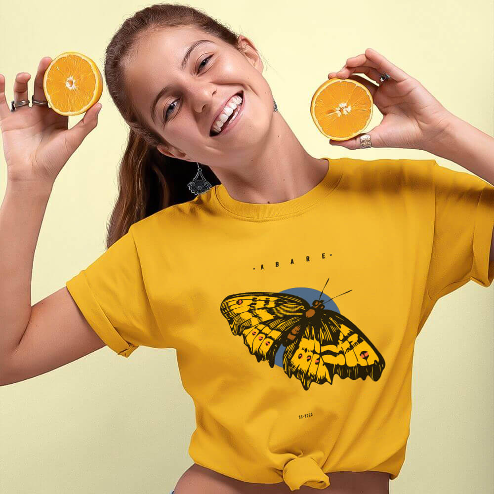 Woman holding orange slices wearing gold butterfly shirt