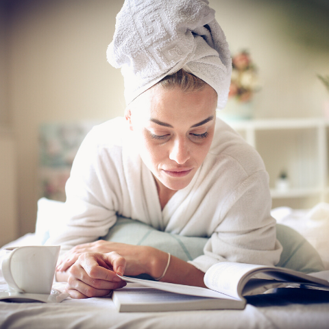Lady reading after having a shower with hair in a towel