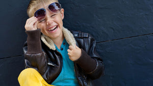Young boy laughing wearing sunglasses and leather jacket.