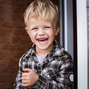 Smiling young boy wearing a flannel shirt.