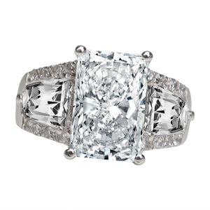 RADIANT CUT EMERALD CENTER CUBIC ZIRCONIA FEATURING A GLEAMING ARRAY OF TAPERED BAGUETTES ON EACH SIDE