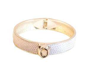 Shimmering centered oval jeweled designer style bracelet bangle finished with a snakeskin-like texture accent in gold-tone 629B-82033