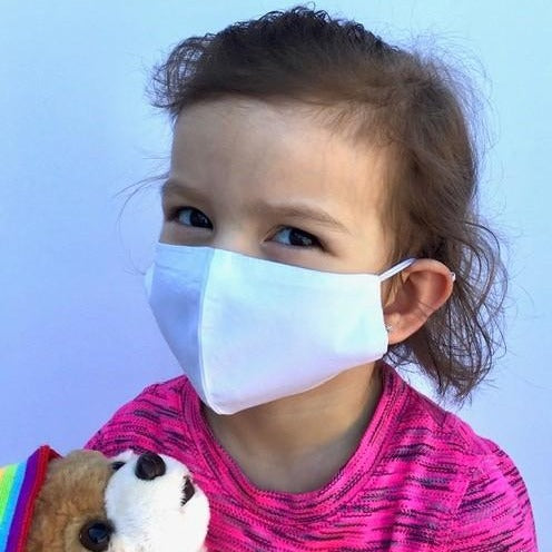 Child holding teddy bear wearing reusable 100% cotton face mask to help minimize the spread of germs and infection