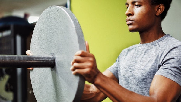 Man loading iron plate onto barbell