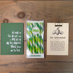Gin Letterbox gift set comprised of a notebook with gin caption, a set of Gin & Elderflower drinks stirrers and a sign with sayings about Gin