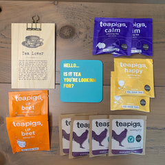 Tea Drinker Letterbox Gift Set comprising of a range of individually wrapped teabags, a humorous coaster and a wooden sign with lots of quotes about tea on it.