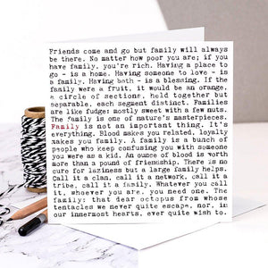 A white square greeting card which is filled with black text. The text is in a typewriter font. It features lots of thoughtful and humorous phrases about family life. These include 'a family is a bunch of people who keep confusing you with someone you were as a kid' and 'Having a place to go - is a home. Having someone to love - is a family'. The phrase family is written in red once to highlight the focus of the card.
