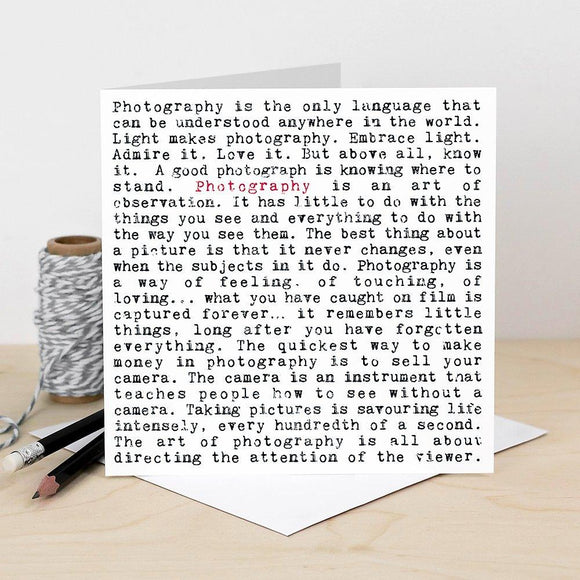 A white square greeting card which is filled with black text. The text is in a typewriter font. It features lots of humorous phrases and inspiring quotes about photography including 'photography is the only language that can be used anywhere in the world' and 'the quickest way to make money in photography is to sell your camera'. The word photography is written in red once to highlight the focus of the card.