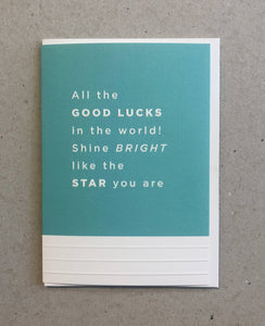 A greeting card. The top three quarters is printed in a turquoise. Text in this area says 'All the good lucks in the world! Shine bright like the star you are. The text is white and embossed. The bottom of the quarter of the card is unprinted and white. It has 3 horizontal, embossed narrow lines.