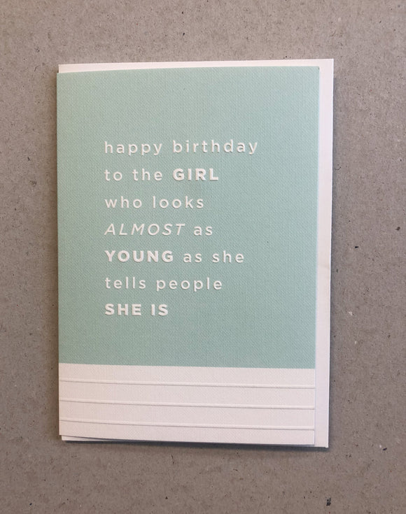 A greeting card. The top three quarters is printed in a pale blue. Text in this area says 'happy birthday to the Girl who looks almost as young as she tells people she is'. The text is white and embossed. The bottom of the quarter of the card is unprinted and white. It has 3 horizontal, embossed narrow lines.