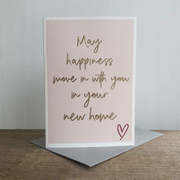 A greeting card which has a printed blush background. On the card in a large, handwritten font is the words 'May happiness move in with you in your new home'. This sentiment is embossed and gold foiled. On the bottom right of the card is a dark red, printed heart outline.