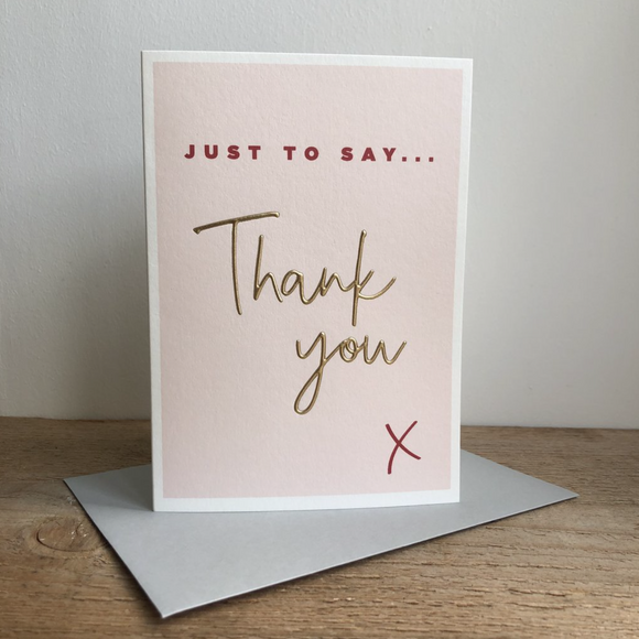 A greeting card which is printed with a blush coloured background. The text at the top says 'Just to Say' and is printed in a dark red. A large Thank You in a handwritten font takes up half the card and is embossed and gold foiled. At the bottom right of the card is a printed red x.