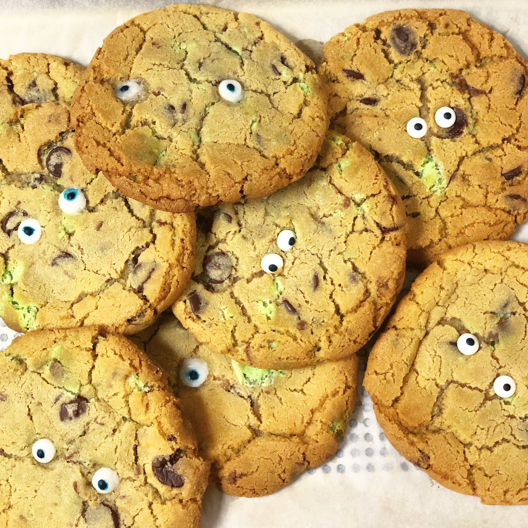 A heap of golden brown large cookies, with mint choc chip pieces and white sugar googly eyes.