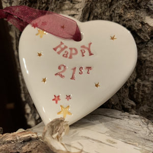 Hand painted ceramic heart featuring star design and the sentiment 'Happy 21st'  Handmade in the UK using clay, glaze and paint sourced locally.  Material:  Ceramic
