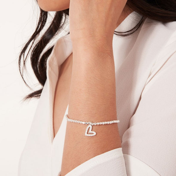 Joma Jewellery 'a little' bracelet with sparkling heart charm, presented on a sentiment card which reads:  'I couldn't say I do without you'
