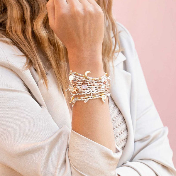 Joma Jewellery bracelet scattered with precious little keepsake charms, including shining moon, a little starburst and a pavé accented charm.   Beautifully packaged in it's own little box which reads 'One In A Million'