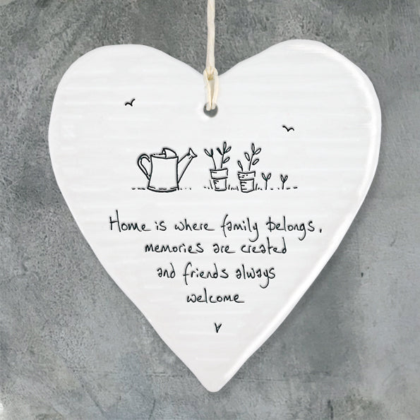 White Hanging Porcelain 'Wobbly' Heart from East of India which reads:  'Home is where family belongs, memories are created and friends always welcome '  The heart features an engraved illustration in East of India's unique style.
