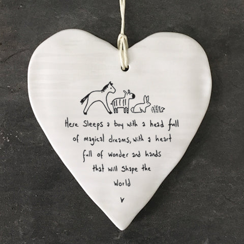 White Hanging Porcelain 'Wobbly' Round Heart baby gift from East of India which reads:  'Here sleeps a boy with a head full of magical dreams, a heart full of wonder and hands that will shape the world.'  The heart features an engraved illustration in East of India's unique style.  Material:  Porcelain