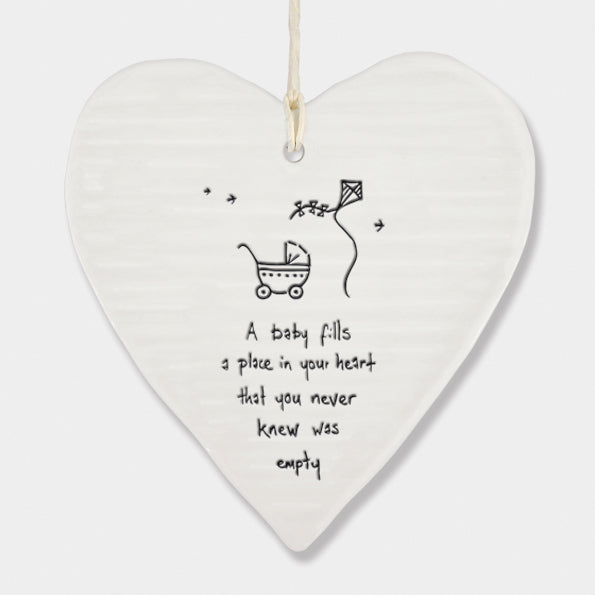 White Hanging Porcelain 'Wobbly' Round Heart baby gift from East of India which reads:  'A Baby fills a place in your heart that you never knew was empty.'  The heart features an engraved illustration in East of India's unique style.