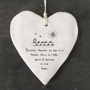 White Hanging Porcelain 'Wobbly' Round Heart from East of India which reads:  'Because someone we love is in heaven there is a little piece of heaven in our home.'  The heart features an engraved illustration in East of India's unique style.