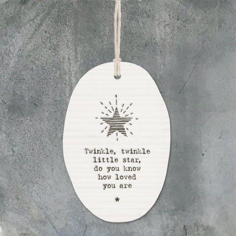White Hanging Porcelain Ornament from East of India which reads:  'Twinkle' twinkle little star, do you know how loved you are.'  The oval shaped hanger also features a star illustration in East of India's unique style.