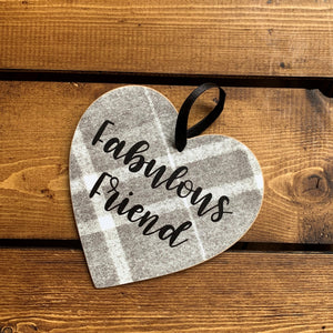 Hanging wooden heart on grey printed tartan with black ribbon and the sentiment: 'Fabulous friend'
