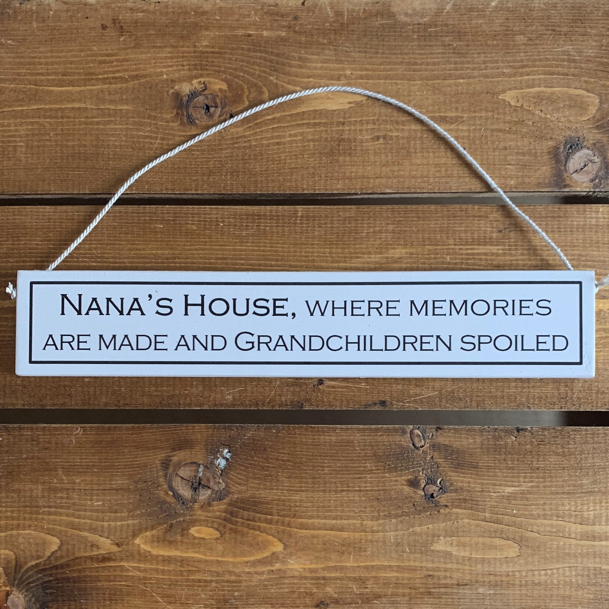 Rustic hanging wooden sign - hand painted with the printed slogan:  'Nana's house, where memories are made and grandchildren spoiled'